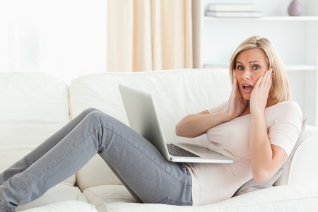 Woman having trouble with her laptop in her living room Stock Photo - 11229259