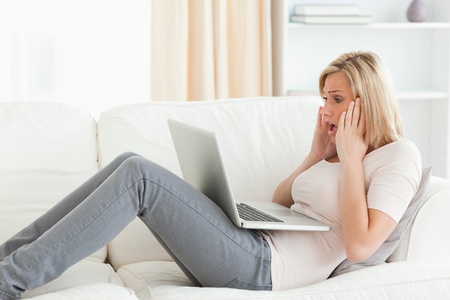 Blonde woman having trouble her laptop in her living room Stock Photo - 11229271