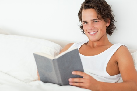 Man holding a book in his bedroom Stock Photo - 11192258