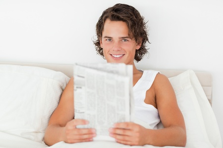 Young man holding a newspaper in his bedroom photo