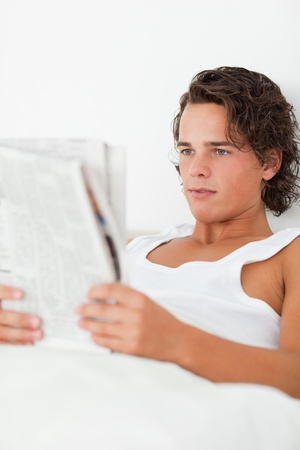 Portrait of a young man reading a newspaper in his bedroom Stock Photo - 11230483