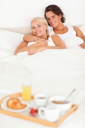 Couple lying on a bed with the breakfast served on a tray photo