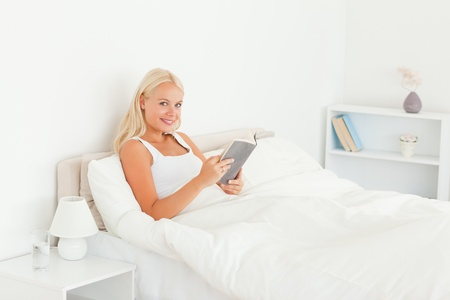 Woman reading a book in her bedroom photo