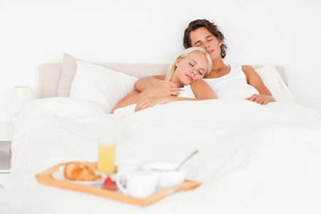 Sleeping couple with the breakfast put on a tray with the camera focus on the models photo
