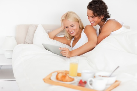 Couple using a tablet computer in their bedroom photo