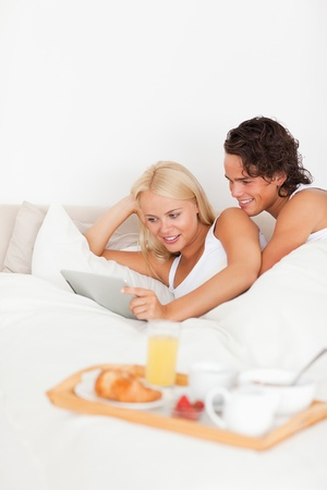 Portrait of a couple using a tablet computer in their bedroom photo