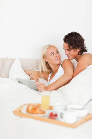 Portrait of a lovely couple using a tablet computer in their bedroom photo