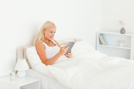 Young woman reading a book in her bedroom photo