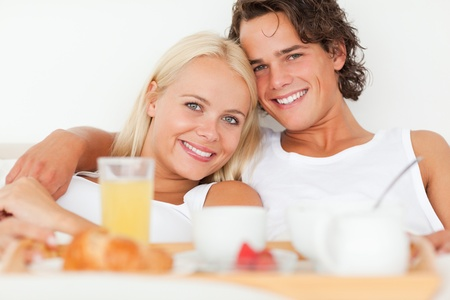 Close up of a smiling couple having breakfast in their bedroom photo
