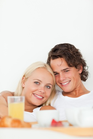 Portrait of a smiling couple having breakfast in their bedroom photo