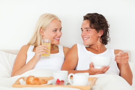 Smiling couple having breakfast in their bedroom photo
