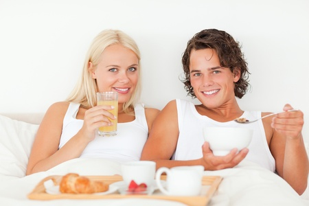 Beautiful couple having breakfast in their bedroom photo