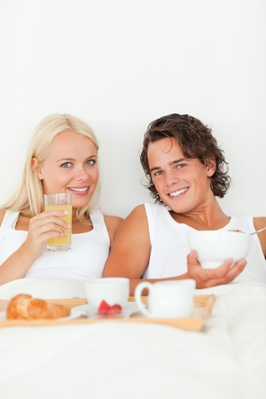 Portrait of a beautiful couple having breakfast in their bedroom photo