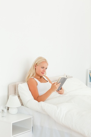 Gorgeous woman reading a book in her bedroom photo
