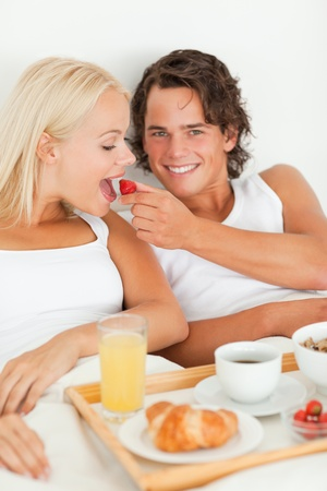 Portrait of smiling man giving a strawberry to his girlfriend in their bedroom photo