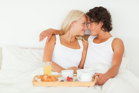 In love couple having breakfast in their bedroom photo