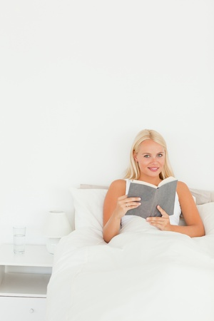 Portrait of a woman holding a book in her bedroom photo