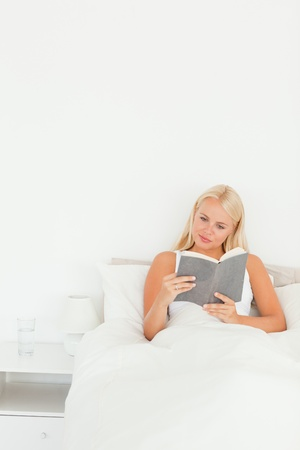 Portrait of a cute woman reading a book in her bedroom photo