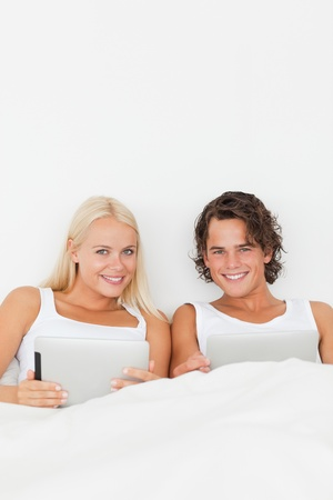 Portrait of a couple with tablet computers in their bedroom photo