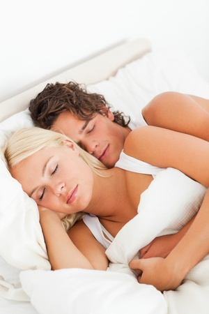 Couple hugging while sleeping in their bedroom photo