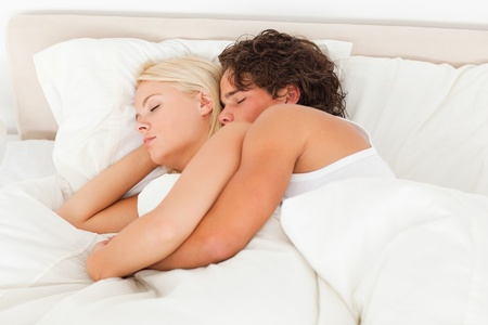 Calm couple hugging while sleeping in their bedroom photo