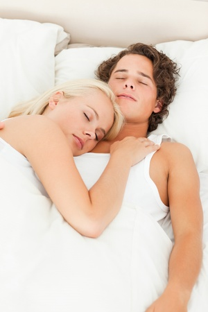 Portrait of a cute couple sleeping in their bedroom photo