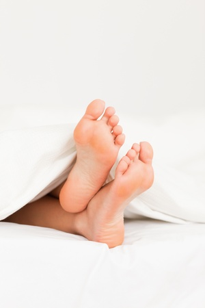 bare foot: Portrait of feet in a bed against a white background