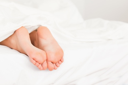 siesta: Two feet in a bed against a white background