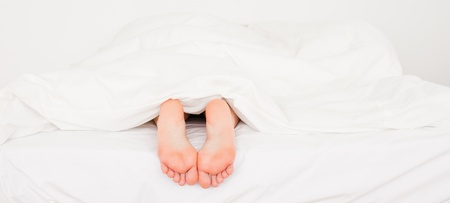 Two white feet in a bed Stock Photo - 11206240
