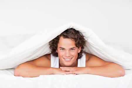 Man under a duvet in a bed photo