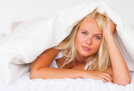 Blonde woman under a duvet in her duvet photo
