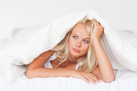 wrapped up: Woman under a duvet in her bedroom Stock Photo