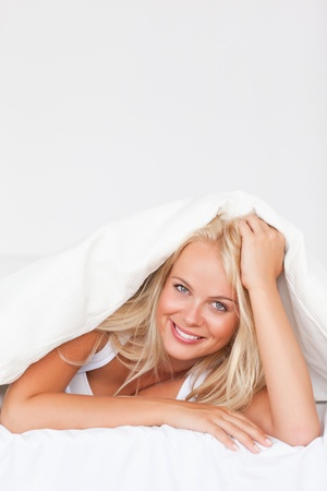 Portrait of a woman under a duvet in her bedroom photo
