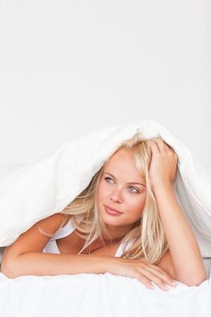 Portrait of a dreaming woman under a duvet photo