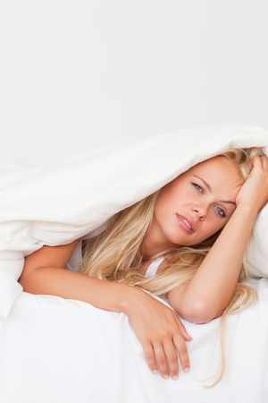 wrapped up: Portrait of a woman waking up under a duvet