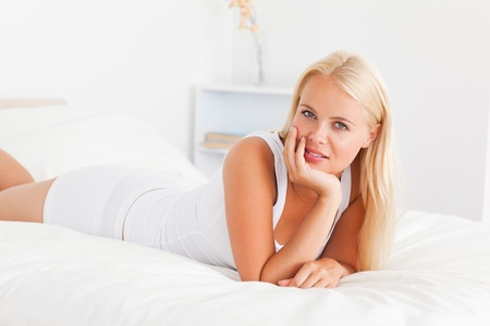 Woman posing on her bed while looking at the camera Stock Photo - 11233056