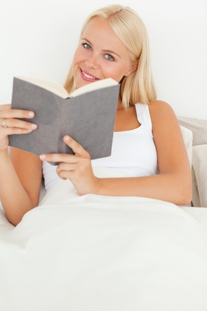 Portrait of a smiling woman holding a book while looking at the camera photo