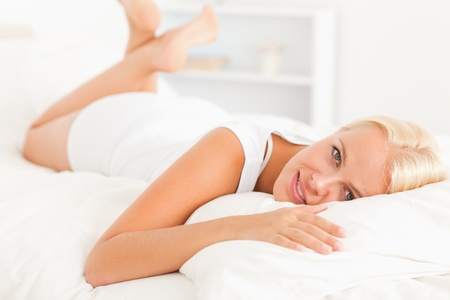 Lovely woman lying on her bed looking at the camera Stock Photo - 11207478