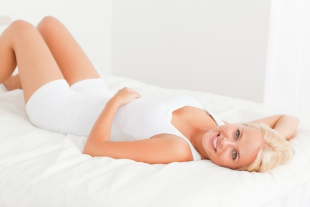 bedding indoors: Woman lying on her back in her bedroom Stock Photo