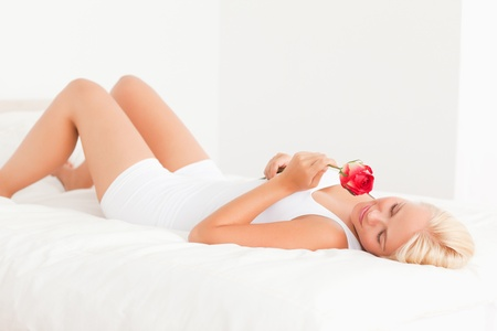 Serene woman smelling a flower in her bedroom photo