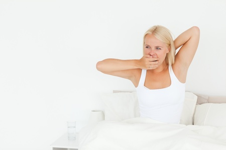 Woman yawning on her bed looking away from the camera photo