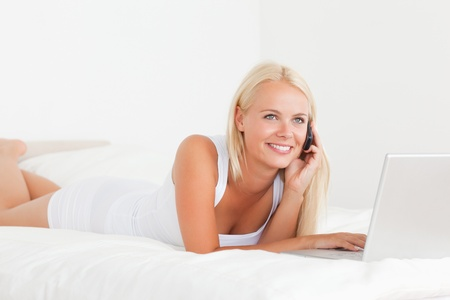 Smiling woman on the phone with a notebook in her bedroom photo