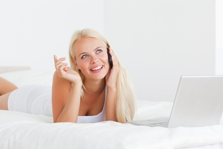 Smiling woman speaking to the phone with a laptop in her bedroom photo