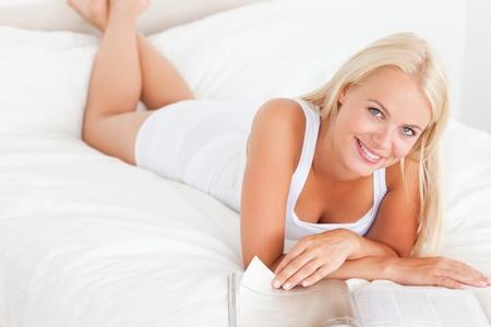 mujeres felices: Sonriente mujer con una revista en su dormitorio