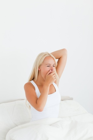 Portrait of a woman yawning in her bedroom photo