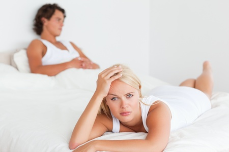 Upset couple after an argument on their bed photo