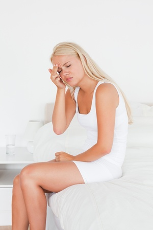 Woman having a headache while sitting on her bed photo