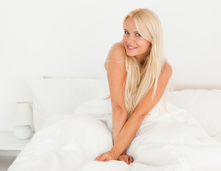 Woman sitting on her bed looking at the camera with a knowing smile photo