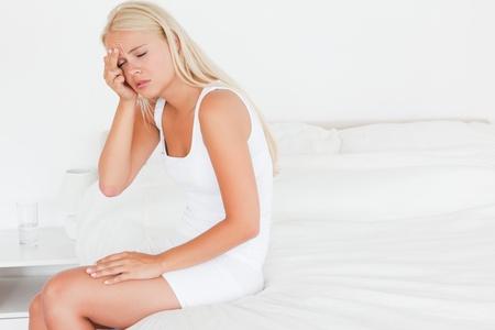 Beautiful woman having a headache in her bedroom photo