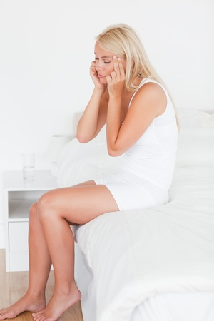 Portrait of a woman having a headache in her bedroom photo